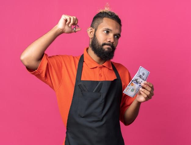 制服を着てはさみを上げ、ドルを持って横を見て混乱している若いアフリカ系アメリカ人の男性床屋