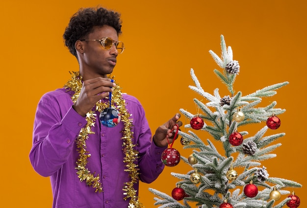 Confused young afro-american man wearing glasses with tinsel garland around neck standing near decorated christmas tree holding christmas baubles looking at tree isolated on orange wall
