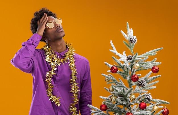 Смущенный молодой афро-американский мужчина в очках с мишурной гирляндой на шее стоит возле украшенной елки на оранжевом фоне