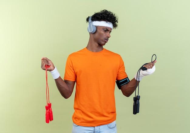 緑の背景に分離された縄跳びを保持し、見てヘッドフォンでヘッドバンドとリストバンドと電話の腕章を身に着けている混乱した若いアフリカ系アメリカ人のスポーティな男