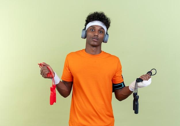 緑の背景に分離された縄跳びを保持しているヘッドフォンとヘッドバンドとリストバンドと電話の腕章を身に着けている混乱した若いアフリカ系アメリカ人のスポーティな男