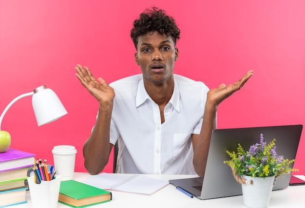 Giovane studente afroamericano confuso seduto alla scrivania con gli strumenti della scuola che tiene le mani aperte isolate sul muro rosa
