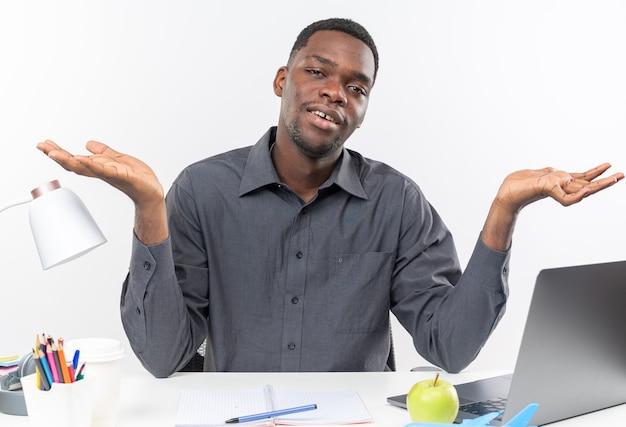 Giovane studente afroamericano confuso seduto alla scrivania con gli strumenti della scuola che tiene le mani aperte isolate sul muro bianco