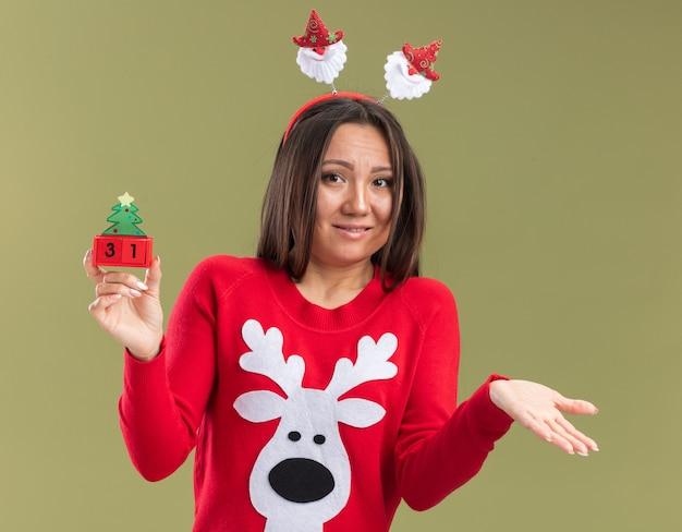 Confusa giovane ragazza asiatica indossando il cerchio dei capelli di natale che tiene la mano di diffusione del giocattolo di natale isolata su fondo verde oliva