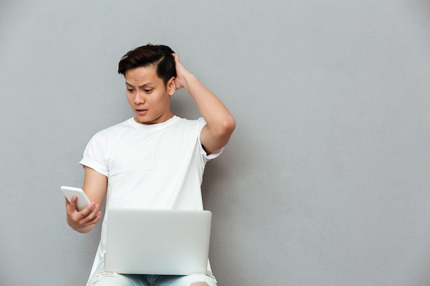Confused young asian man looking at mobile phone.