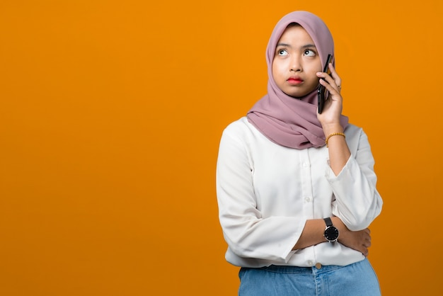 Confused young asian woman talking on smartphone on yellow