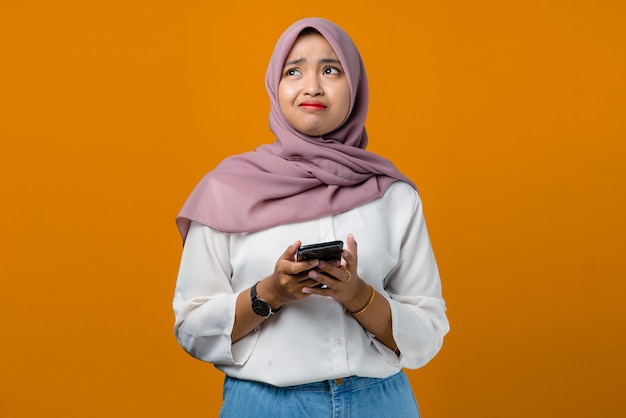 Confused young asian woman using mobile phone on yellow