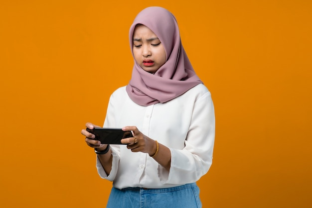Confused young asian woman using smartphone on yellow