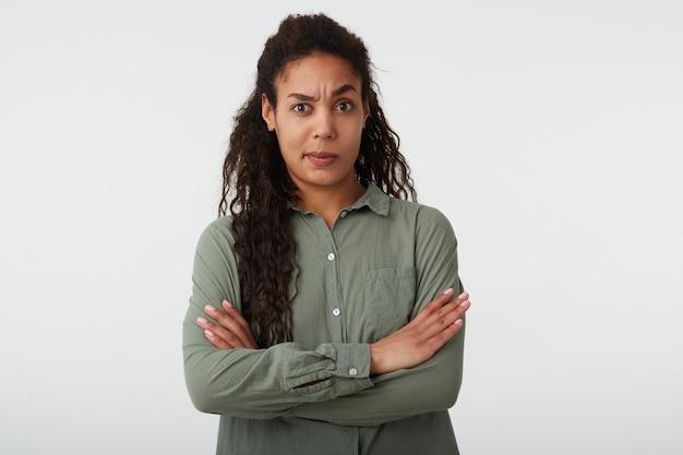 Confuso giovane attraente donna dai capelli scuri ricci mantenendo le mani incrociate e alzando sorpreso sopracciglia mentre guarda la telecamera, in piedi su sfondo bianco