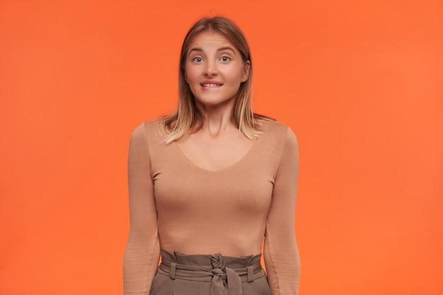 Смущенная молодая привлекательная белоголовая женщина с короткой стрижкой и непринужденной прической кусает нижнюю губу, удивленно глядя вперед, позирует над оранжевой стеной