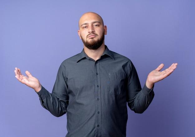 보라색에 고립 된 빈 손을 보여주는 혼란 된 젊은 대머리 콜 센터 남자