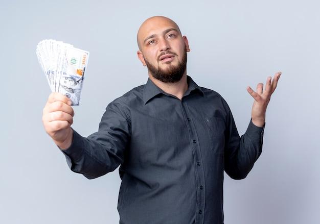 Uomo calvo giovane confuso della call center che allunga i soldi e che mostra la mano vuota che osserva in su isolato su bianco