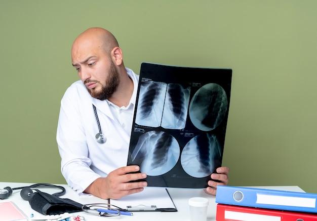 緑の背景に分離されたx線を保持している医療ツールとデスクワークに座っている医療ローブと聴診器を身に着けている混乱した若いハゲの男性医師