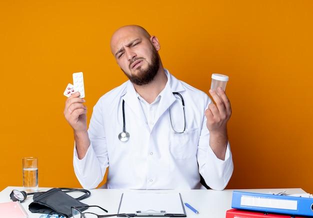 医療用ローブと聴診器を着て仕事机に座っている混乱した若いハゲの男性医師