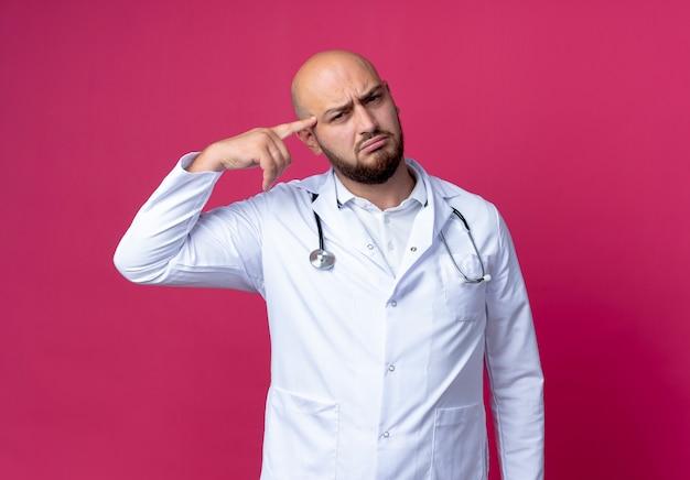 Confuso giovane medico maschio calvo che indossa abito medico e stetoscopio mettendo il dito sulla fronte isolato sulla parete rosa