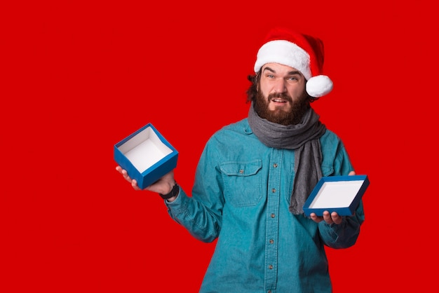 Смущенный молодой бородатый мужчина держит открытую пустую подарочную коробку.