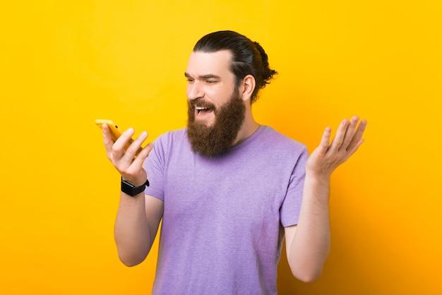 혼란스러운 수염을 기른 젊은이가 들고 있는 전화와 통화하고 있습니다.