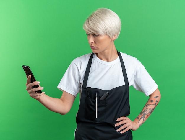 Смущенная молодая красивая женщина-парикмахер в униформе, держащая и смотрящую на телефон, положив руку на бедро, изолированную на зеленой стене
