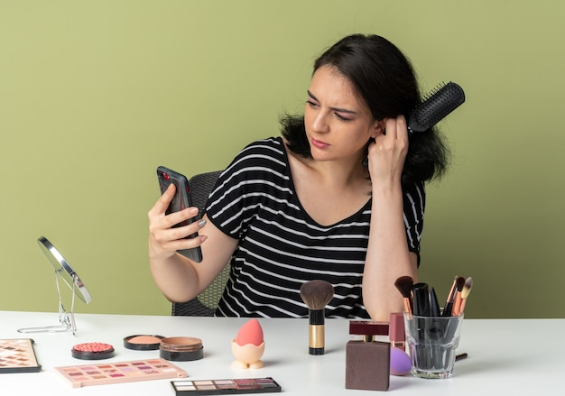 Смущенная молодая красивая девушка сидит за столом с инструментами для макияжа, держа расческу и глядя на телефон в руке, изолированной на оливково-зеленой стене