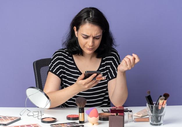 Смущенная молодая красивая девушка сидит за столом с инструментами для макияжа, держа кисть для макияжа и глядя на телефон в руке, изолированной на синей стене