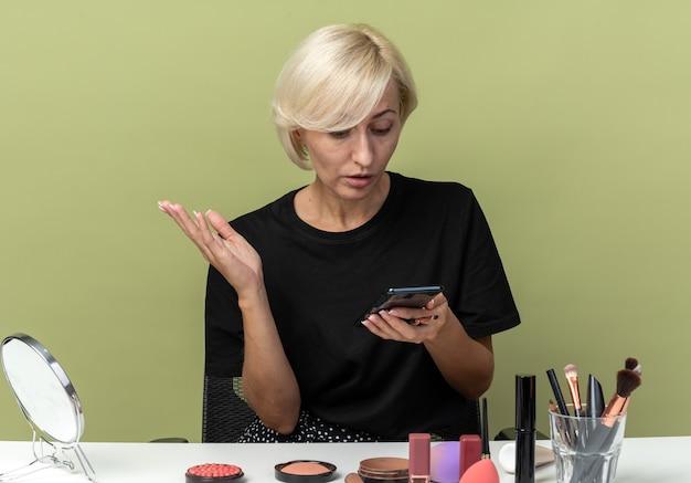 Смущенная молодая красивая девушка сидит за столом с инструментами для макияжа, глядя на телефон в руке, изолированной на оливково-зеленой стене
