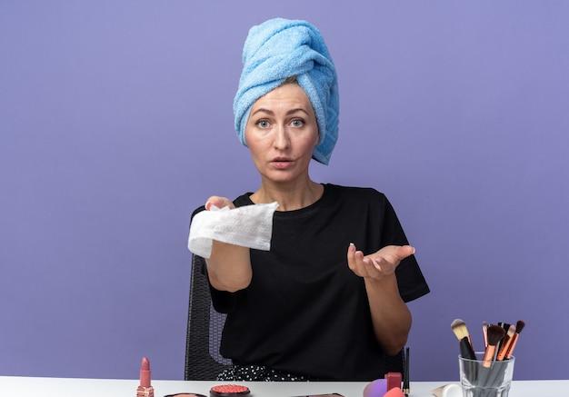 Смущенная молодая красивая девушка сидит за столом с инструментами для макияжа, вытирая волосы полотенцем, протягивая салфетку перед камерой, изолированной на синей стене