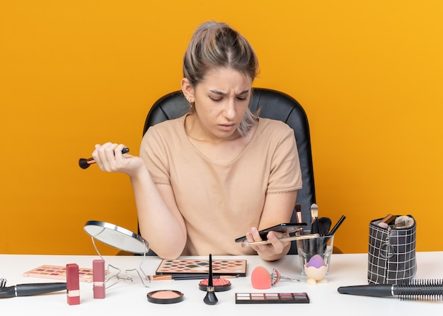 La giovane bella ragazza confusa si siede al tavolo con gli strumenti per il trucco tenendo il pennello per il trucco e guardando il telefono in mano isolato sul muro arancione
