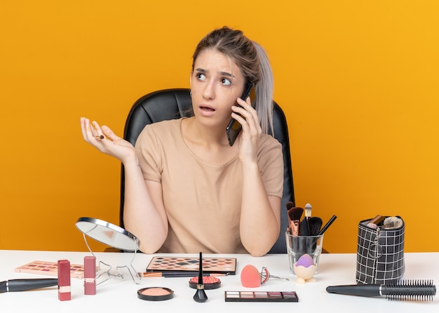La giovane bella ragazza confusa si siede al tavolo con gli strumenti per il trucco che tengono il pennello per il trucco parla al telefono diffondendo la mano isolata sul muro arancione