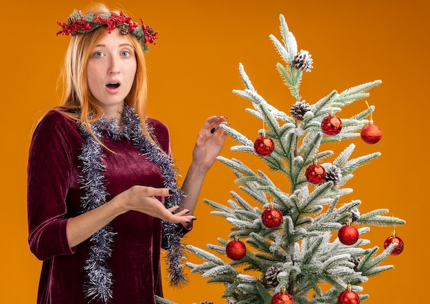 오렌지 배경에 고립 목에 갈 랜드와 빨간 드레스와 화 환을 입고 크리스마스 트리 근처에 서 혼란 젊은 아름 다운 소녀