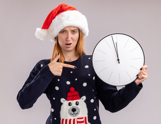 Confusa giovane bella ragazza che indossa il cappello di natale che tiene e punti all'orologio di parete isolato su priorità bassa bianca