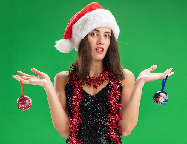 Confused young beautiful girl wearing christmas hat with garland on neck holding christmas tree balls spreading hands isolated on green background