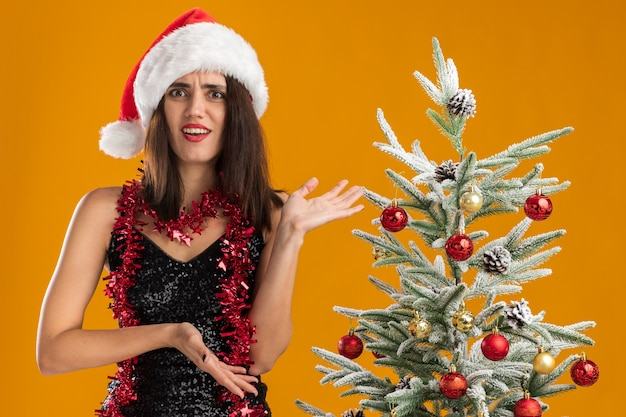 Смущенная молодая красивая девушка в новогодней шапке с гирляндой на шее, стоящая рядом с елкой и руками на дереве, изолирована на оранжевом фоне