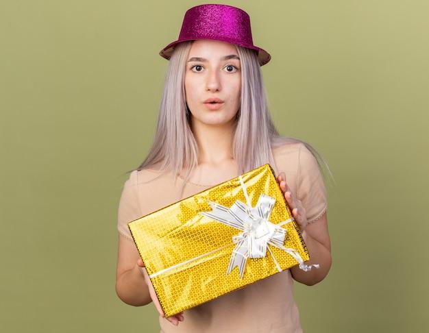 Смущенная молодая красивая девушка в партийной шляпе держит подарочную коробку