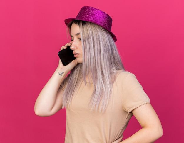 파티 모자를 쓰고 혼란스러운 젊은 아름다운 소녀는 전화로 말한다