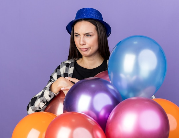 Confused young beautiful girl wearing party hat standing behind balloons