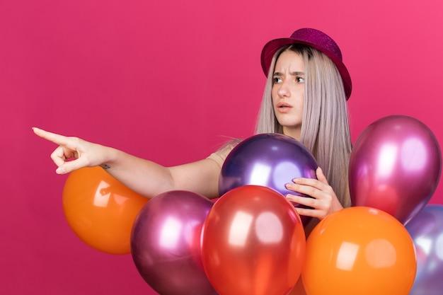 분홍색 벽에 격리된 쪽에 풍선 포인트 뒤에 서 있는 치과 교정기가 있는 파티 모자를 쓰고 혼란스러운 젊은 아름다운 소녀