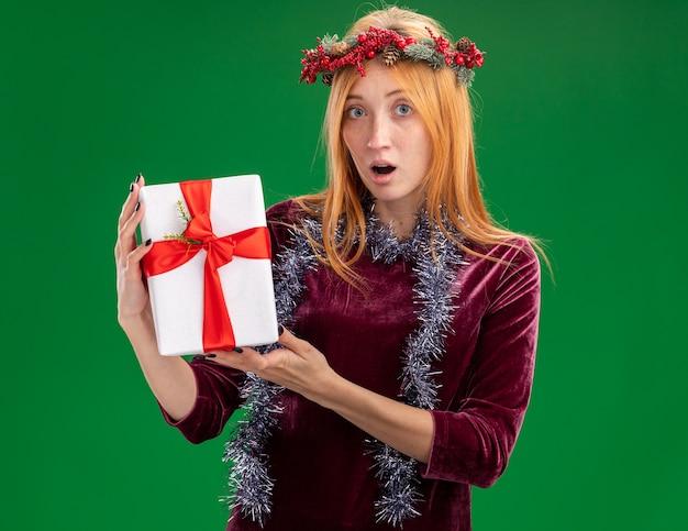 Confuso giovane bella ragazza che indossa un abito rosso con la corona e la ghirlanda sul collo che tiene il contenitore di regalo isolato su priorità bassa verde