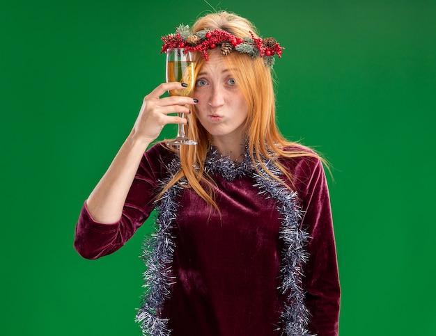 Giovane bella ragazza confusa che porta vestito rosso con la corona e la ghirlanda sul collo che tiene un bicchiere di champagne intorno alla fronte isolato su priorità bassa verde