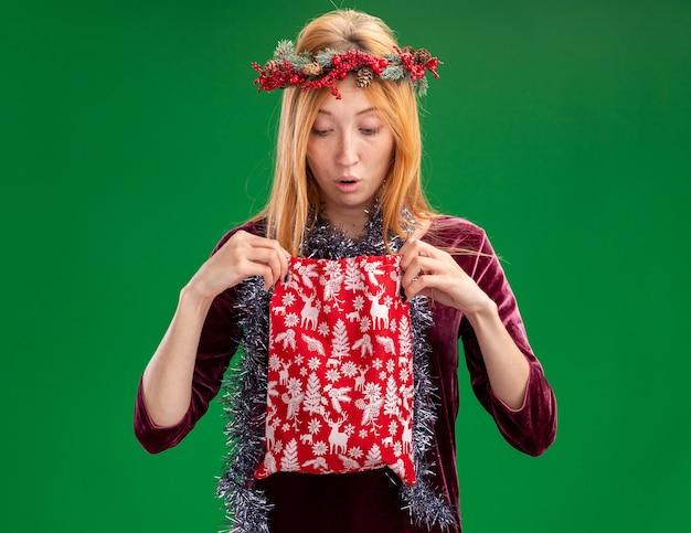 Confusa giovane bella ragazza che indossa un abito rosso con la corona e la ghirlanda sul collo che tiene ed esamina la borsa di natale isolata su fondo verde