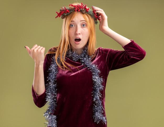 Confusa giovane bella ragazza che indossa un abito rosso con corona e ghirlanda sui punti del collo a lato isolato su sfondo verde oliva con spazio di copia