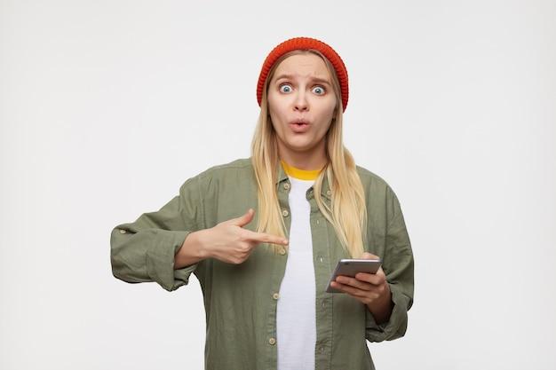 Confuso giovane bella signora bionda dai capelli lunghi arrotondando sorprendentemente i suoi occhi azzurri mentre mostra con l'indice sul suo telefono cellulare, isolato sull'azzurro