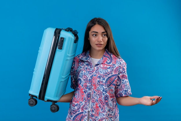 Confused young beautiful traveler woman holding travel suitcase looking aside doubtful shrugging shoulders standing over isolated blue space