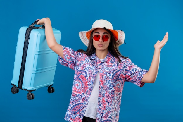 Confused young beautiful traveler woman in summer hat wearing red sunglasses holding travel suitcase  doubtful shrugging shoulders standing over isolated blue space