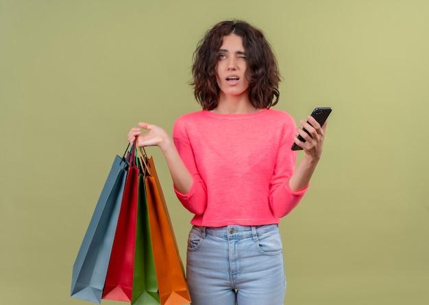 Giovane bella donna confusa che tiene i sacchetti di cartone e il telefono cellulare sulla parete verde isolata