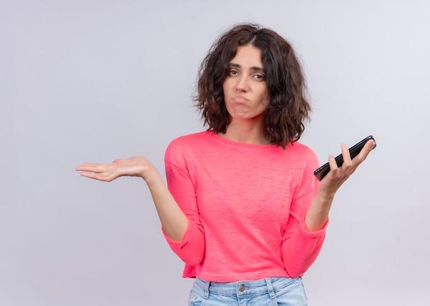 Giovane bella donna confusa che tiene il telefono cellulare e che mostra la mano vuota sulla parete bianca isolata