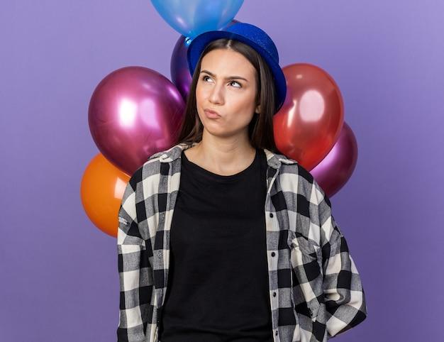 青い壁に分離された前の風船に立っているパーティーハットを身に着けている混乱した若い美しい女性