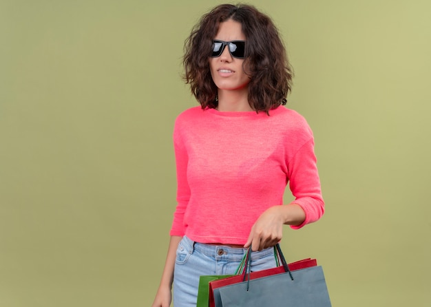 Giovane bella donna confusa che indossa occhiali da sole e che tiene i sacchetti di cartone sulla parete verde isolata con lo spazio della copia