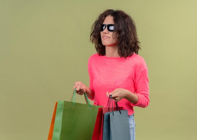 Giovane bella donna confusa che indossa occhiali da sole e che tiene i sacchetti di cartone sulla parete verde isolata