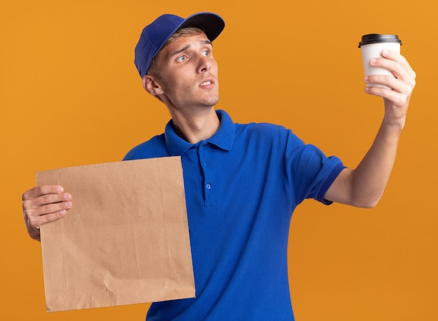 Confused young blonde delivery boy holds paper package and looks at cup on orange