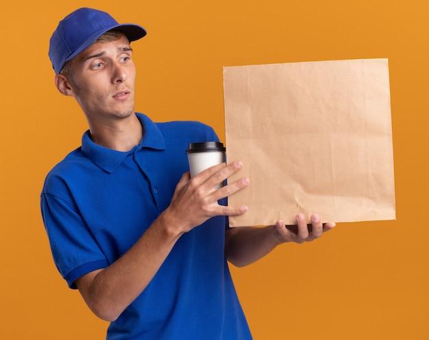 Il giovane ragazzo delle consegne biondo confuso tiene la tazza da asporto e guarda il pacchetto di carta isolato sulla parete arancione con lo spazio della copia